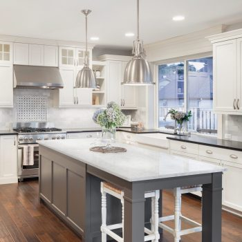 kitchen featuring gray kitchen island and white countertop with all white cabinets